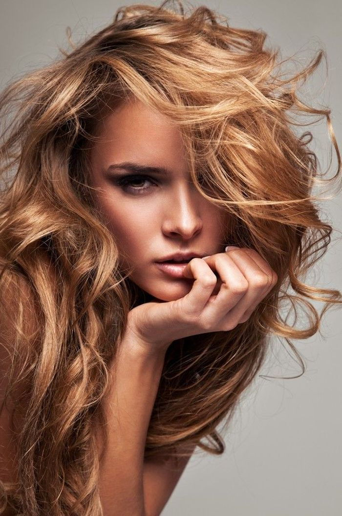 attractive woman with blond-reddish curly hair, dark eyes