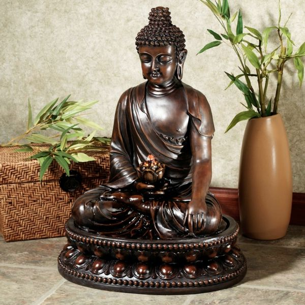 Buddha Fountain a-vase-with-a-green-plant-next
