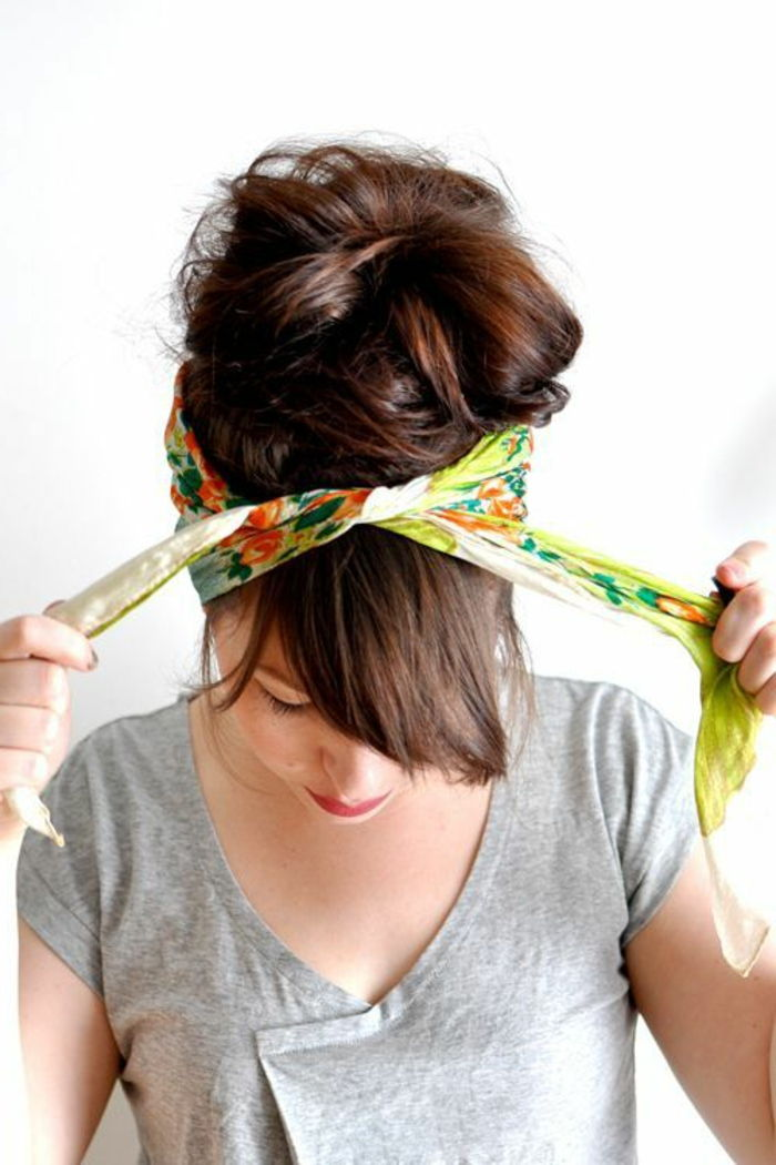 lady with brown hair, colorful bandana and gray blouse