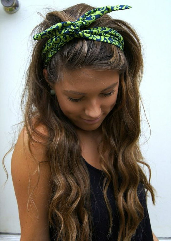 lady with long, curly, brown hair and blue bandana with green pattern