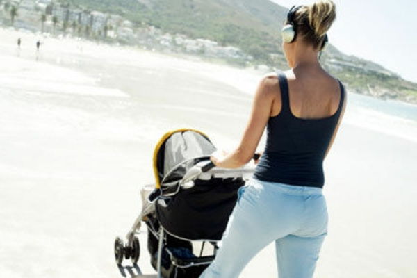 a-mother-makes-walk-with-their-kind-in-stroller-the-beach