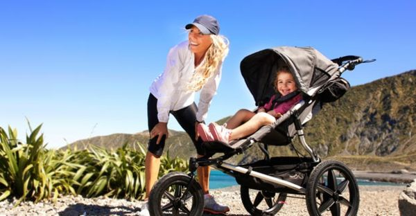 a-beautiful-blonde-mother-with-the-kind-in-stroller-makes-walk