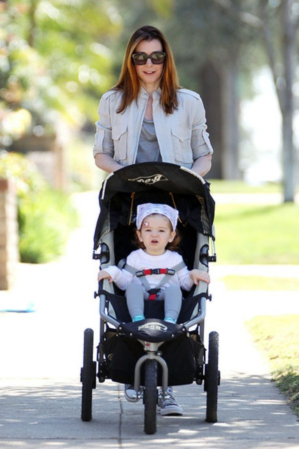 super-beautiful-mother-makes-a-walk-in-park-with-her-daughter-in-stroller